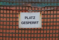 Closed german tennis court platz gesperrt sign hanging from net in winter Stock Photo