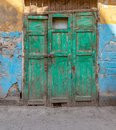 Green wooden grunge weathered abandoned door on dirty wall painted in yellow and blue Royalty Free Stock Photo