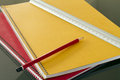 Closed notebooks with pencil and slat in yellow red Royalty Free Stock Photo