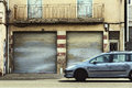 Closed parking and car on a cityscape european family in movement urban still with doors in the background Royalty Free Stock Images