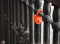 Closed red padlock in the form of heart locked on bridge. Royalty Free Stock Photo