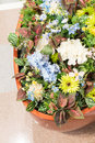 Closed up colorful artificial flowers in ceramic clay pot on mar