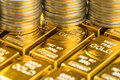 Closed up shot of shiny gold bars with stack of coins as busines Royalty Free Stock Photo