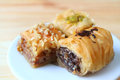Closed up Three Types of Baklava Sweets on White Plate Served on Wooden Table Royalty Free Stock Photo