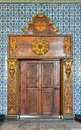 Closed wooden engraved aged door framed by golden ornate wooden frame on Turkish ceramic tiles wall with floral blue patterns Royalty Free Stock Photo