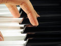 Closeup active hand playing piano as black white keys being pressed to produce melodious notes Royalty Free Stock Photos