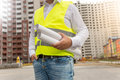 Closeup of architect in safety vest posing with blueprints at ne Royalty Free Stock Photo