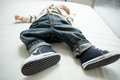 Closeup of baby boy feet in jeans and sneakers lying on bed Royalty Free Stock Photo