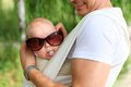 Closeup of baby boy in sling while his father is trying sunglasses on him humorous aspect Stock Photos