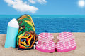 Closeup beach with sandals towel and suntan lotion Royalty Free Stock Photo