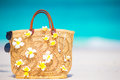 Closeup beautiful bag with frangipani flowers and sunglasses on white beach Royalty Free Stock Photo