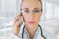 Closeup of a beautiful female doctor using mobile phone Royalty Free Stock Photo