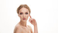 Closeup beauty portrait of young adorable blonde woman touching her cheekbone by finger on white studio background girl Stock Photo