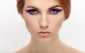 Closeup beauty portrait of a young beautiful calm redhead woman with violet eyes makeup Royalty Free Stock Photo