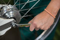 Closeup of bicycle mechanic with a wrench repairing bike wheel Royalty Free Stock Photography