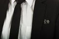 Closeup black suit jacket chest pocket with glass chess pieces sitting inside, white shirt and tie visible
