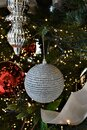 Silver white ornament hanging from greenery and surrounded by additional red and silver ornaments and ribbon. Royalty Free Stock Photo