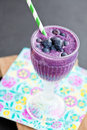 Closeup of blueberry milk smoothie in glass with striped straw on paper serviette on wooden serving tray Royalty Free Stock Image