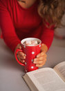 Closeup on book and cup of hot chocolate in hand of young woman red dress Royalty Free Stock Photography