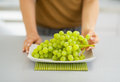 Closeup on branch of grapes on plate and woman tearing off grape high resolution photo Royalty Free Stock Photography