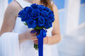 Closeup of bride hands holding beautiful wedding bouquet with blue roses. Concept of floristics Royalty Free Stock Photo