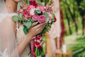 Closeup of bride hands holding beautiful wedding bouquet with white and pink roses. Concept of floristics Royalty Free Stock Photo