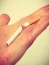 Closeup of broken cigarette on male hand.