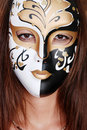 Closeup brunette wearing a gold white  black mask Royalty Free Stock Photography