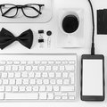 Closeup of business objects in order on white desk overhead essentials office black and Stock Photography