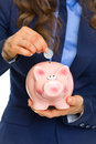 Closeup on business woman putting coin into piggy bank isolated white Royalty Free Stock Images