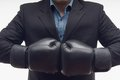 Closeup businessman in boxing gloves isolated on portrait of black white background Stock Photo