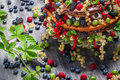 Closeup of cake wild fresh berry fruits on old table Royalty Free Stock Photography