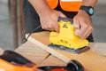 Closeup carpenter sanding wood of hand plank with electrical machine Stock Photos