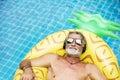 Closeup of caucasian senior man in the pool with headphones
