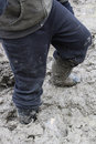 Closeup of a child walking in thick mud