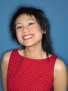 Closeup of a chinese woman grinning portrait against blue background Stock Photo