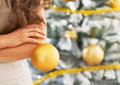 Closeup on christmas ball in hand of woman young standing near tree Stock Photo