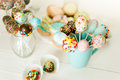 Closeup of colorful cake pops in cups on white wooden desk