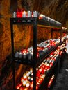 Closeup of colorful candles burning in the tunnel of Covadonga, Cangas de Onis, Asturias, Spain. Spirituality Royalty Free Stock Photo