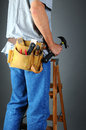 Closeup of a contractor standing on a wooden ladder holding his hammer vertical format over a light to dark gray background man is Royalty Free Stock Photography