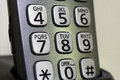 Closeup of cordless phone numbers and letters on buttons sitting Royalty Free Stock Photo