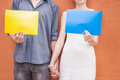 Closeup couple holding hands and holding frames at wall background Royalty Free Stock Photo