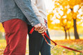 Closeup on couple holding leash together in park young autumn Stock Photography