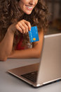 Closeup on credit card in hand of woman usign laptop kitchen Stock Photos