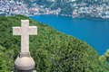 Closeup of a cross on a church rooftop the top mount san salvatore with mountain panorama landscape view in lugano lake como Stock Images