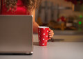 Closeup on cup of hot chocolate and woman usign laptop in red dress Royalty Free Stock Photography