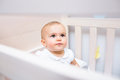 Closeup of a cute baby looking up in crib the at home Stock Photo