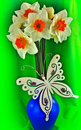 A closeup of daffodils in a vase tin butterfly decoration Royalty Free Stock Photos
