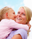 Closeup of a daughter kissing her smiling mother Royalty Free Stock Image