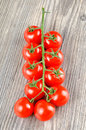 Closeup of a delicious red ripe cherry tomatoes with stem on wooden kitchen table Royalty Free Stock Photo